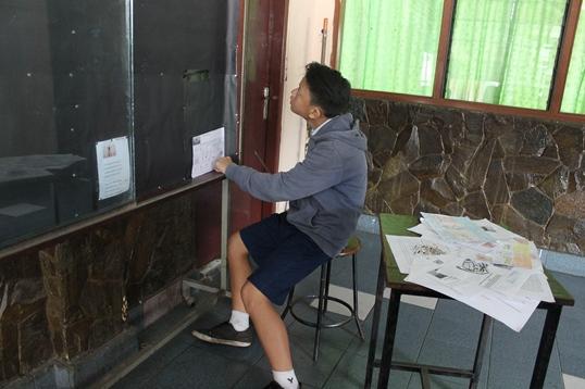 Tim Redaksi (Vio) sedang membereskan papan publikasi.